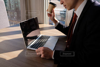 ラップトップコンピュータを使ってテーブルに座っている男性の写真・画像素材[2962993]