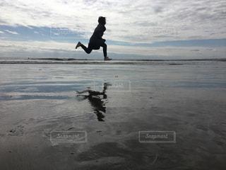 浜辺で空を飛んでいる男の写真・画像素材[2981526]