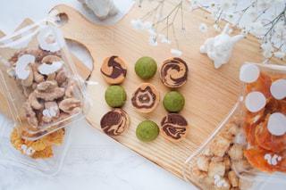 食べ物の皿をトッピングした木製のテーブルの上に座っているケーキの写真・画像素材[3021092]