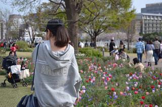 花の前に立っている人の写真・画像素材[1127347]
