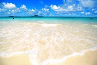 海の横にある砂浜に座っている男の写真・画像素材[1131846]
