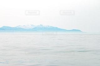 凪の海と雪山の写真・画像素材[1227359]