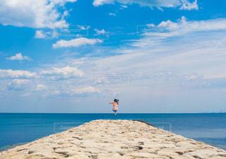 海の横にある砂浜のビーチの上に立っている人の写真・画像素材[1315954]