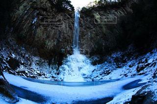 滝雪の側に木で覆われた斜面の写真・画像素材[1455025]