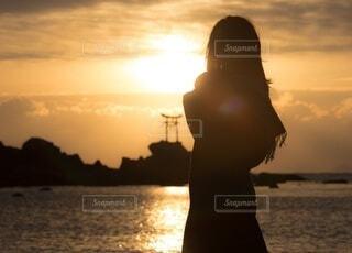 水の体に沈む夕日の前に立っている人の写真・画像素材[3986476]
