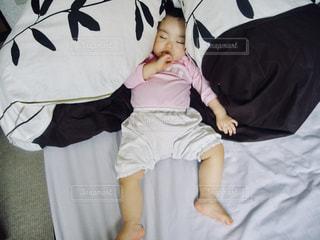 布団に埋もれ指しゃぶりしながら眠る赤ちゃん。の写真・画像素材[1148470]