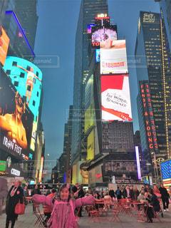 バック グラウンドでタイムズ ・ スクエアと通りを歩く人々 のグループの写真・画像素材[1174111]