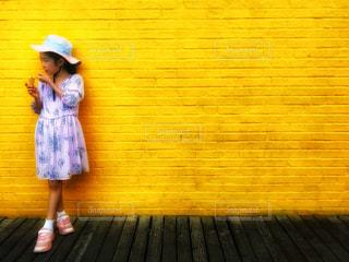 黄色い壁の前でアイスを食べる女の子の写真・画像素材[1359470]