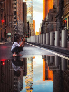 水溜まりに映る秋の夕空と女の子の写真・画像素材[1465967]