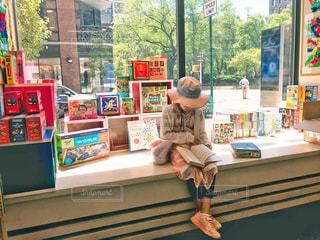 書店の窓際で本を読む女の子の写真・画像素材[1547580]