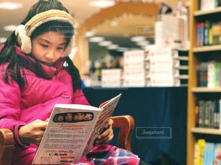 児童書コーナーで集中して本を読む女の子の写真・画像素材[1597145]