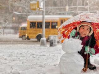 初雪で雪だるまを作った女の子の写真・画像素材[1620880]