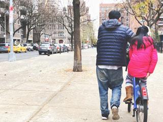 自転車に乗る娘と自転車を押す父の写真・画像素材[1660297]