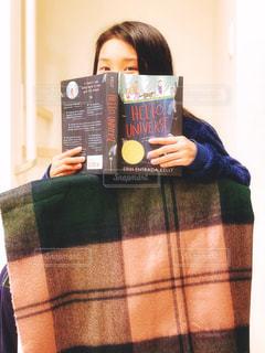 本から恥ずかし気に顔を覗かせる少女の写真・画像素材[1667941]