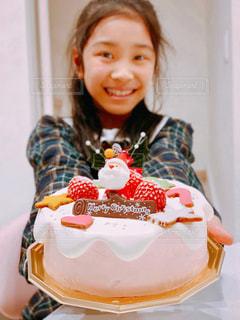 バースデー ケーキでテーブルに座っている女性の写真・画像素材[1695636]