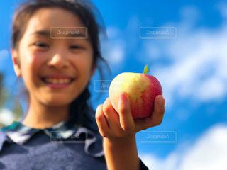 青空の下、林檎を手にする少女の写真・画像素材[1798301]