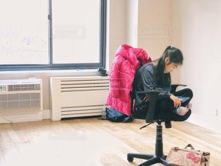 椅子に胡座をかいて座る少女の写真・画像素材[1827856]