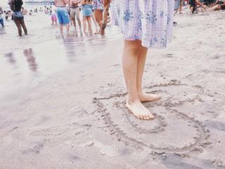 砂浜のダブルハートの中に立つ少女の写真・画像素材[1841556]