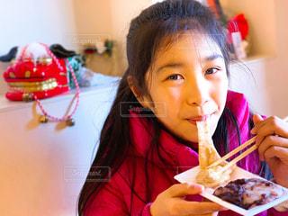 カメラ目線で伸びる餅を頬張る少女の写真・画像素材[1857694]