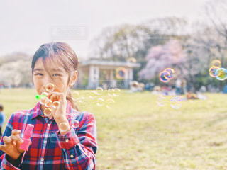桜をバックにシャボン玉で遊ぶ少女の写真・画像素材[1989231]