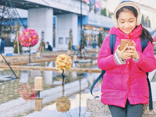 スマホを見て微笑む少女の写真・画像素材[2329166]