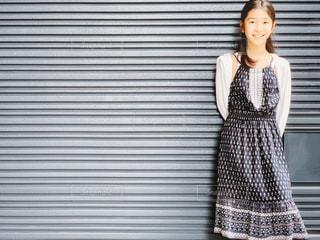 壁に寄りかかる笑顔の女の子の写真・画像素材[2419598]