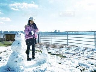 雪だるまの親子を作って嬉しそうな女の子の写真・画像素材[4206222]