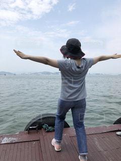 水の体の横に立っている人の写真・画像素材[1282158]