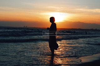バック グラウンドで夕焼けのビーチに立っている人の写真・画像素材[1289360]