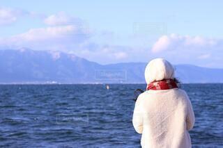 水の体の隣に立っている男の写真・画像素材[4131787]