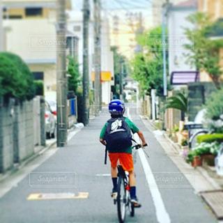 自転車に乗って出かける少年のうしろ姿の写真・画像素材[1164795]