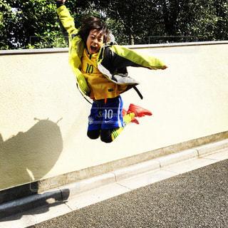 子ども,ジャンプ,子供,笑顔,こども,少年,10,サッカー少年,黄色いジャケット,青いパンツ