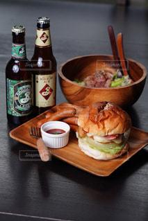 食べ物の皿をトッピングした木製のテーブルの上のビールのボトルの写真・画像素材[2826946]