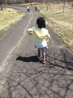 長い道を歩く少女の写真・画像素材[1158385]