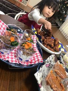 食物と一緒にテーブルに座っている少女の写真・画像素材[1646184]