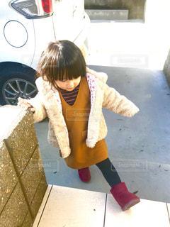 歩道の上に座っている少女の写真・画像素材[1678777]