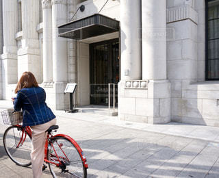 女性,建物,自転車,屋外,街,都会,人,後姿,歩道,通り,うしろ姿,ジージャン,赤い自転車