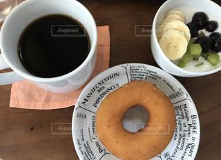 コーヒーとドーナツとキウイ、バナナ、ブルーベリーのフルーツヨーグルトの写真・画像素材[1166300]
