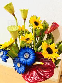 黄色い花の上に座っている花で満たされた花瓶の写真・画像素材[2140735]