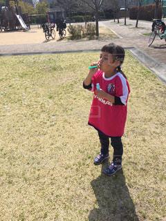 草の中に立っている小さな男の子の写真・画像素材[1164313]