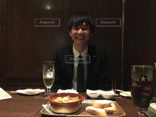 ワイングラスとテーブルに座って、カメラで笑顔の人の写真・画像素材[1371320]