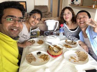食品のプレートをテーブルに座っている人々 のグループの写真・画像素材[1172601]