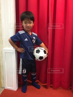 カーテンの前に立っている少年の写真・画像素材[1310501]