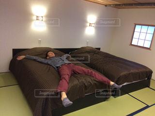 部屋のベッドに横になっている人の写真・画像素材[1212858]