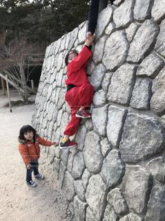岩の壁に立っている少年の写真・画像素材[2183449]