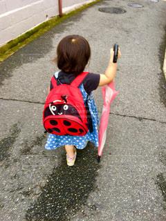 子ども,傘,屋外,ピンク,赤,道路,人物,人,地面,雨上がり,梅雨,若い,リュック,少し