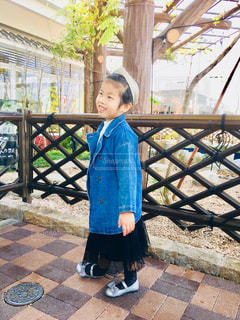 フェンスの前に立っている少年の写真・画像素材[1676236]