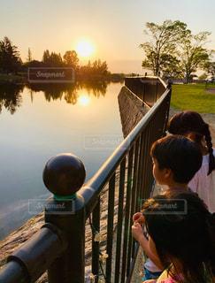 3人,風景,空,屋外,太陽,水面,池,反射,光,樹木,人,映る,眺める