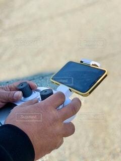 手,撮影,指,手持ち,人物,人,地面,ポートレート,趣味,ドローン,ライフスタイル,手元,操縦,携帯電話,スマート フォン