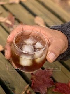 お酒,枯れ葉,ベンチ,手,氷,指,手持ち,人物,リラックス,人,カップ,ポートレート,爪,ライフスタイル,手元,飲料